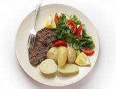 Pan-grilled pepper minute steak served with a salad of fresh leaves, tomato, cucumber and lemon with