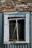 Broken window on a dilapidated steel shed