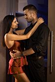 stock photo of sark  - Young man and sexy woman in silk pyjamas embracing in bedroom door - JPG