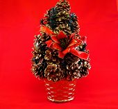 Christmas tree made with pinecones on red background