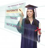 stock photo of post-teen  - Attractive Young Mixed Race Female Graduate in Cap and Gown Choosing Doctorate Post Graduate Path Button on Futuristic Translucent Panel - JPG