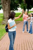 stock photo of bye  - Beautiful young female college student waving good bye to her friends - JPG