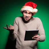 undecided young santa man holding a tablet pad computer on green background