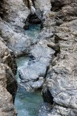 Narrow Mountain Stream Flows Among Blue Striped Rocks