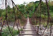 stock photo of luzon  - A rusty steel cable suspension bridge with a wooden plank walkway stretches across a mountain stream near Subic Luzon Philippines - JPG