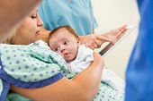 Cute newborn babygirl with loving mother in hospital