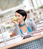 Female student with green apple studies sitting at the desk at the reading hall of the library. Lear