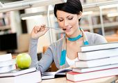 Woman with green apple surrounded with piles of books reads sitting at the table at the library. Tra