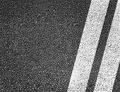 Asphalt road background. Double lines closeup
