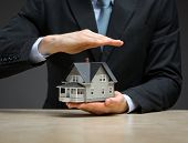 Close up of hands, one is handing little house, another one is covering it. Concept of protection and real estate
