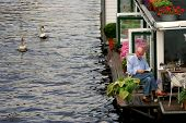 AMSTERDAM - JULY 15: Two white swans passing by houseboat on city canal. Houseboats are high demand