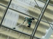 man at work, pressure washing a glass roof