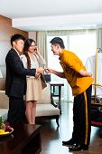 Baggage porter or bellboy or page receiving tip for delivering the suitcase of guests to the hotel room or suite