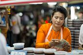 Thai woman eturning the change at the night market in Hua Hin