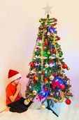 pic of humility  - Boy child praying in front of a Christmas tree - JPG