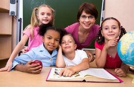 pic of school child  - Portrait of teacher and children looking at camera in the classroom - JPG