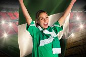 Cheering football fan in green jersey holding nigeria flag against vast football stadium with fans i