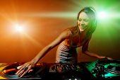 Cute dj woman having fun playing music on vinyl record deck at club party nightlife lifestyle