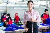 Female Indonesian tailor, dressmaker or designer standing proudly in an Asian textile factory, it is