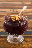 Acai In Glass With Muesli On Wooden Table. Vertical