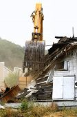 image of track-hoe  - A large track hoe excavator tearing down an old hotel to make way for a new commercial development - JPG