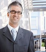 Portrait of happy mid adult caucasian male business advisor. Wearing suit and glasses, looking at ca