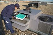 image of hvac  - Worker changing a roof top air exchange units fan belt - JPG