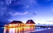 Beach restaurant glowing with bright lights in the night, romantic place for date on tropical island, summer holidays concept
