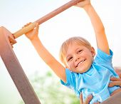 Little boy with fathers help catch up on the horizontal  bar, active childhood, cute small acrobat,