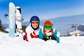 Hugging couple in ski masks lying on the snow
