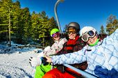 Three happy snowboarders sitting in elevator