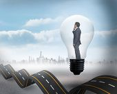 Thinking businessman in light bulb against bumpy road backdrop