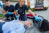 Paramedics checking pulse of unconscious senior man lying on street
