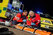 Paramedics giving first-aid to injured motorbike woman driver at night