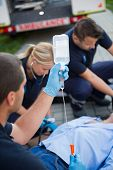 Paramedic team preparing drip for injured patient lying on street
