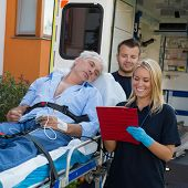 stock photo of stretcher  - Emergency team treating injured elderly patient lying on stretcher outdoors - JPG