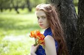 Portrait of beautiful young red hair girl with a bouquet of tulips alive