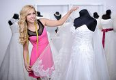 picture of dress mannequin  - Designer wedding dresses measures the dress on a mannequin in her shop - JPG