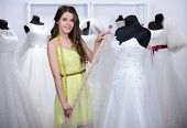 stock photo of dress mannequin  - Designer wedding dresses measures the dress on a mannequin in her shop - JPG