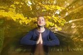 foto of namaste  - Casual dressed young man looking at camera with namaste greeting in autumn park - JPG