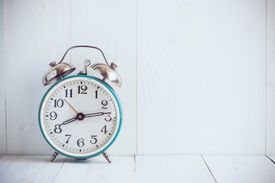 foto of blue-bell  - Big old vintage alarm clock with bells painted white wooden background - JPG