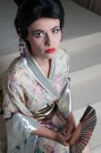 Traditional Japanese geisha woman with extreme makeup and traditional clothing