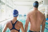 Rear view of a fit male and female swimmers by the pool at leisure center