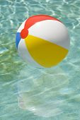picture of pool ball  - Brightly lit shot of a colorful beach ball floating in a swimming pool ready to get played with - JPG