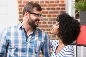 Young casual businessman and woman looking at each other in office