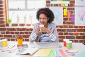 Portrait of smiling female interior designer with coffee cup sitting at office desk