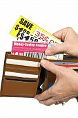 Hand Pulling Coupons Out Of Wallet