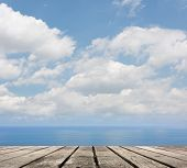Empty wooden deck table with copyspace under sunny cloudy sky in the beach, focus on the wooden ground.