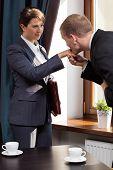 stock photo of hand kiss  - Elegant businessman kissing woman in the hand - JPG