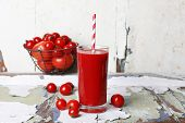 Glass of tomato juice and fresh tomatoes on old wooden table on wall background